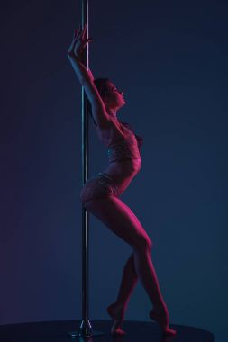 side view of seductive young female dancer leaning at pole on blue