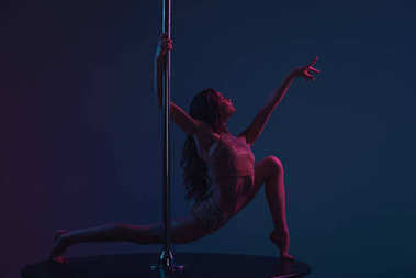 flexible young woman dancing with pole on blue