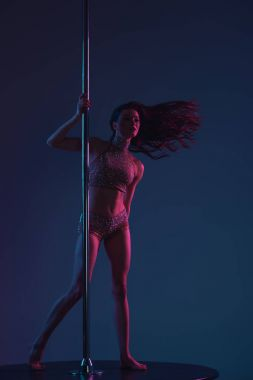 beautiful sporty girl dancing with pole on blue
