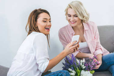 beautiful female friends laughing and using smartphone