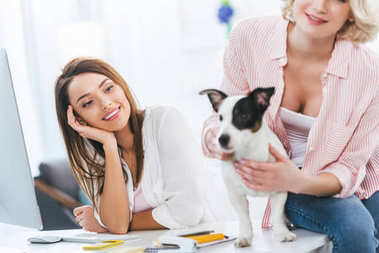 cheerful girls with jack russell terrier dog at home