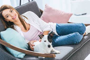 attractive girl with jack russell terrier dog sitting at home