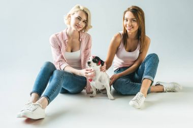 beautiful girls with jack russell terrier dog in red hearts, on white