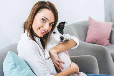 smiling woman with jack russell terrier dog sitting on sofa at home