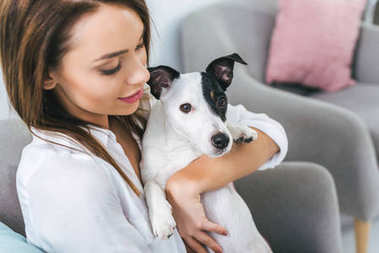 beautiful woman with jack russell terrier dog sitting on sofa