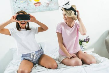beautiful girls having fun and using vr headsets at home