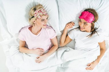 top view of smiling girls in sleeping masks lying on bed