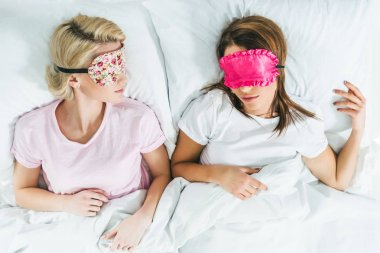 top view of young girls sleeping in masks on bed