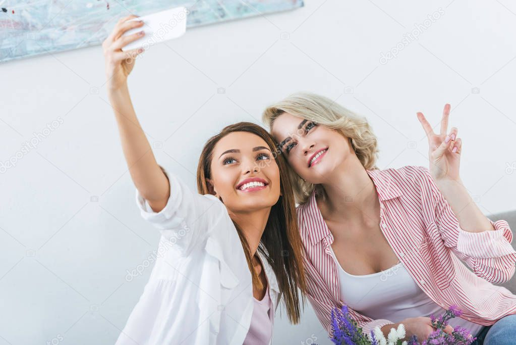cheerful female friends with victory sign taking selfie on smartphone