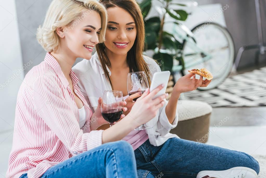 beautiful women with wine and pizza using smartphone