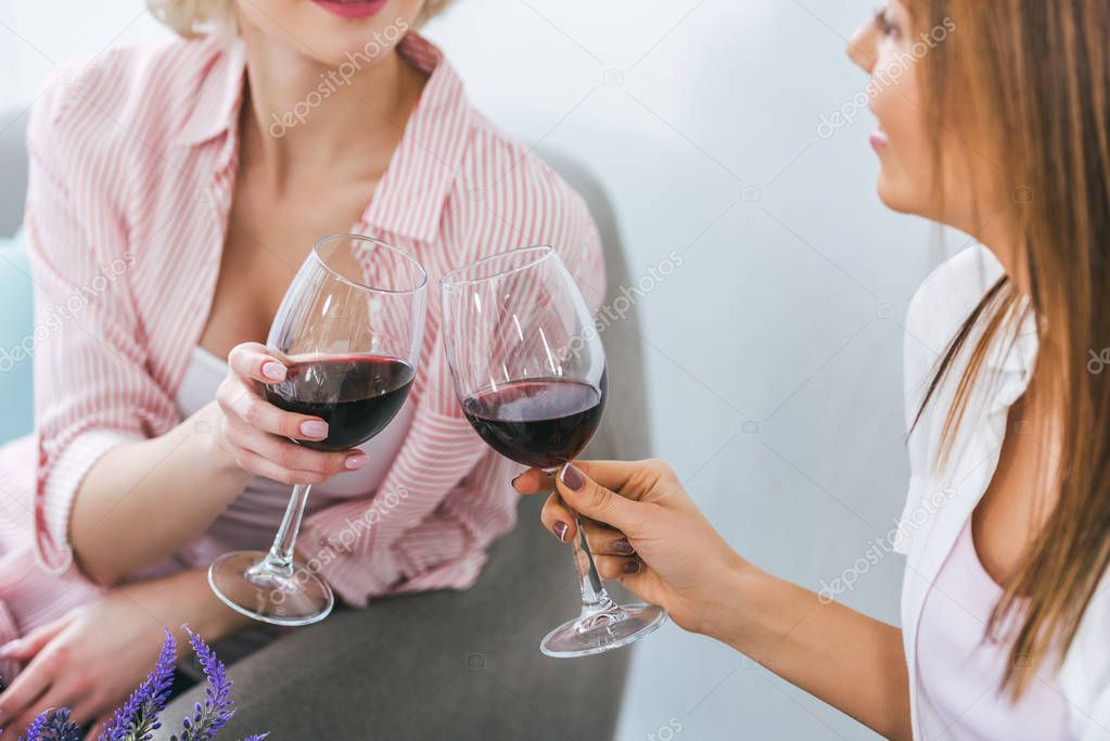 cropped view of girls clinking with wineglasses and spending time together