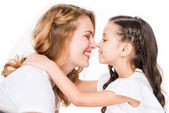 Fotografie cute daughter hugging smiling mother isolated on white