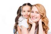 Ať se usmívám, matka a dcera při pohledu na fotoaparát izolované na bílém