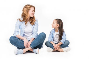 cute kid and mother looking at each other isolated on white