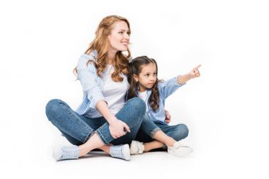 child pointing away while showing something to mother isolated on white