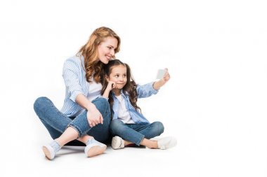 happy mother and daughter taking selfie on smartphone together isolated on white