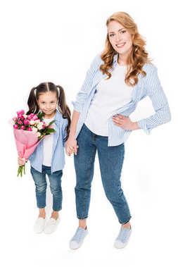 happy mother and little daughter with bouquet of flowers holding hands isolated on white, mothers day holiday concept