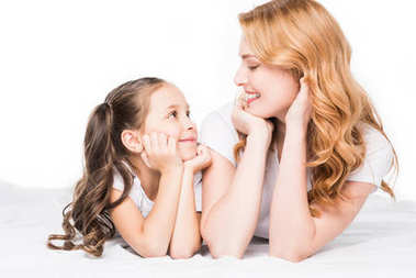 portrait of smiling mother and daughter looking at each other isolated on white