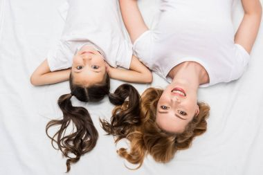 overhead view of smiling mother and daughter lying on bed