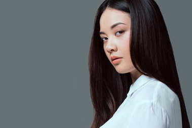 close-up portrait of beautiful asian girl looking at camera isolated on grey