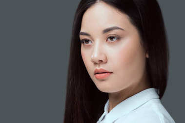 close-up portrait of beautiful young asian woman looking away isolated on grey