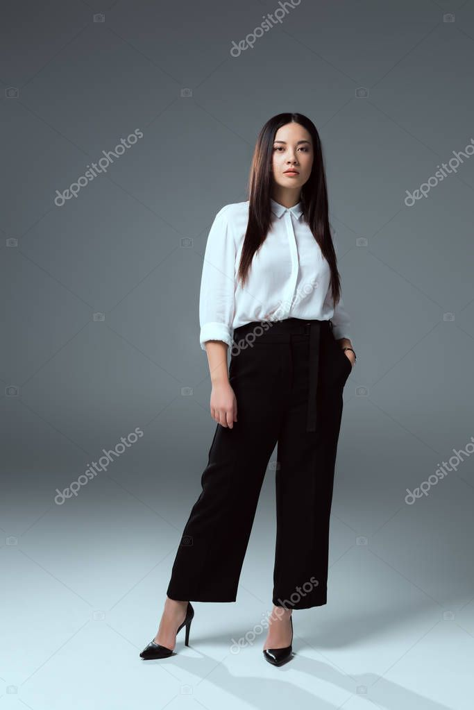full length view of beautiful asian girl standing with hand in pocket and looking at camera on grey