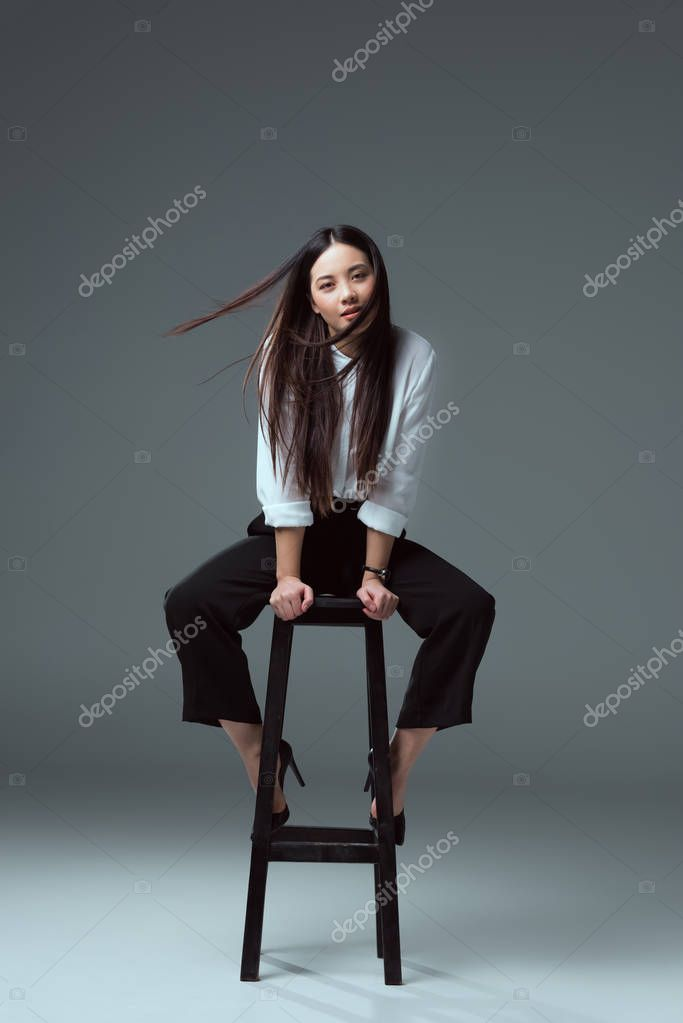 beautiful young asian woman sitting on chair and looking at camera on grey