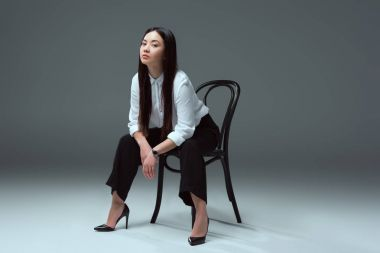 full length view of beautiful young asian woman sitting on chair and looking at camera on grey