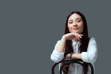 beautiful asian girl sitting on chair and smiling at camera isolated on grey