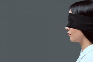 side view of young woman wearing black blindfold isolated on grey
