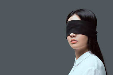 young woman wearing black blindfold isolated on grey