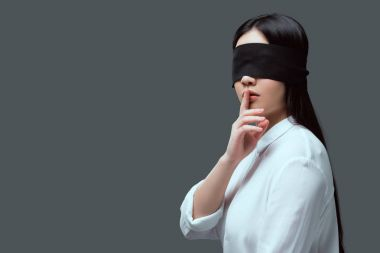 young woman with black blindfold gesturing for silence isolated on grey