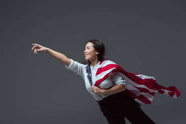 happy young woman with american flag reaching hand and looking away isolated on grey