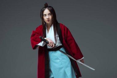 samurai in kimono holding katana sword isolated on grey