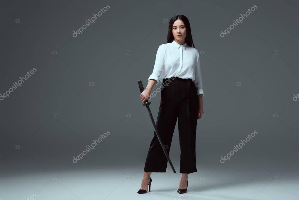 full length view of beautiful young asian woman holding katana and looking at camera on grey