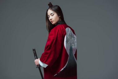young woman in traditional japanese kimono holding katana and looking at camera isolated on grey