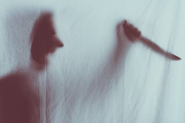 scary blurry silhouette of person screaming and holding knife behind veil