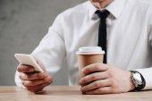 ritagliata colpo delluomo daffari che tiene tazza di carta e lutilizzo di smartphone