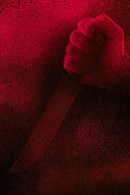 cropped shot of human hand holding knife in red light with glitches