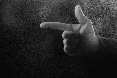 cropped shot of person pointing away with finger in darkness