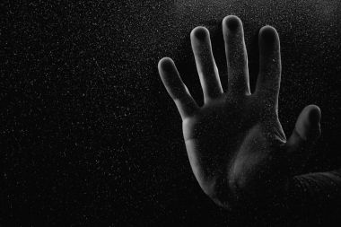 cropped shot of person touching frosted glass with palm in darkness