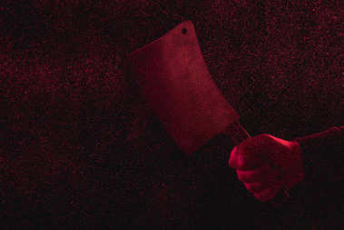 cropped shot of man holding meat knife in red light