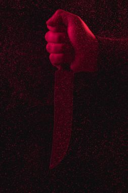 close-up partial view of man holding knife in red light