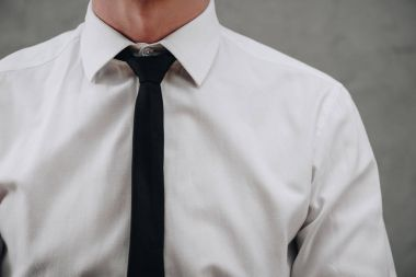 cropped shot of businessman in white shirt and black necktie on grey