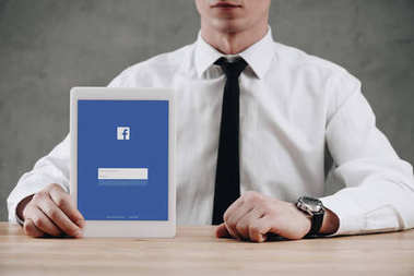 mid section of businessman holding digital tablet with facebook website on screen
