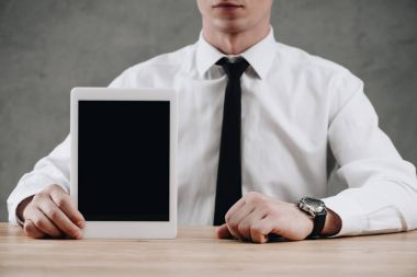 mid section of businessman holding digital tablet with blank screen