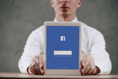 Cropped shot of man holding digital tablet with facebook website on screen stock vector