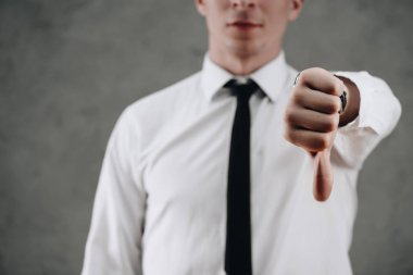 cropped shot of businessman showing thumb down on grey