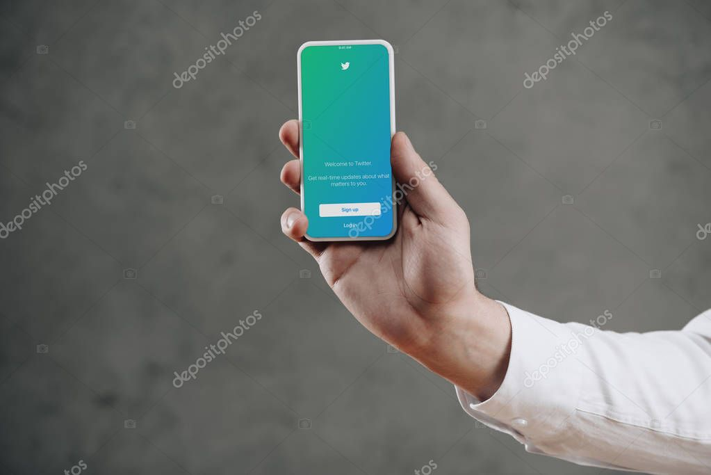 cropped shot of man holding smartphone with twitter application on screen