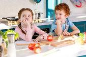 roztomilá dítka v zástěry vaření zeleninový salát spolu v kuchyni